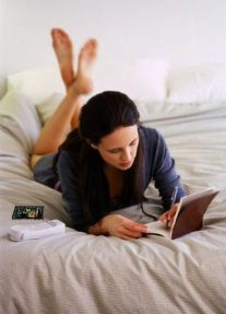 Woman Writing in Diary in Bed